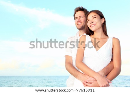 Happy beach couple portrait of beautiful young romantic interracial couple smiling happy embracing on beach during summer vacation. Caucasian man, Asian woman. - stock photo