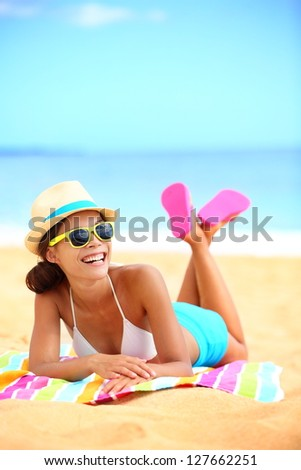 Happy beach woman laughing having fun. Colorful lifestyle image of funky and trendy  young hipster girl lying in sand enjoying summer holiday vacation. Blissful mixed Asian / Caucasian model outdoor - stock photo