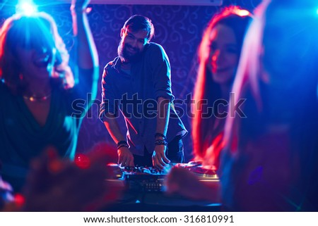 Happy bearded deejay standing by turntables in front of dancing crowd and looking at camera - stock photo