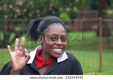 Happy beautiful Africa girl raised OK gesture - stock photo