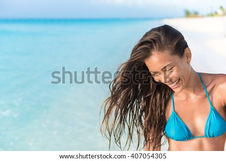 Happy beautiful Asian mixed race ethnic bikini body woman laughing having fun relaxing on tropical summer beach on Caribbean travel holidays. Brunette with healthy hair. - stock photo