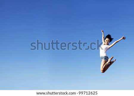 Happy beautiful asian woman jumping with copy space. Shot over clear blue sky can be used to add your text - stock photo