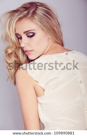 happy beautiful blond girl with curly long hair and smoky eyeshadow makeup wearing pastel beige silk fashion blouse with luxury buttons on the back - stock photo