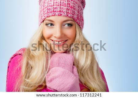 happy beautiful blonde woman wearing pink knitwear over blue background looking to the side - stock photo