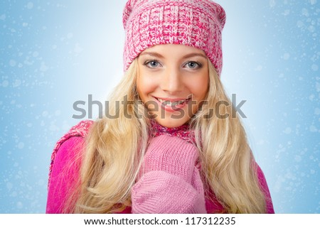 happy beautiful blonde woman wearing pink knitwear over blue background with snow - stock photo
