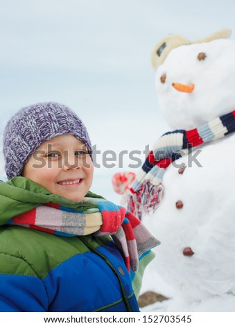 Happy beautiful boy building snowman outside in winter time - stock photo