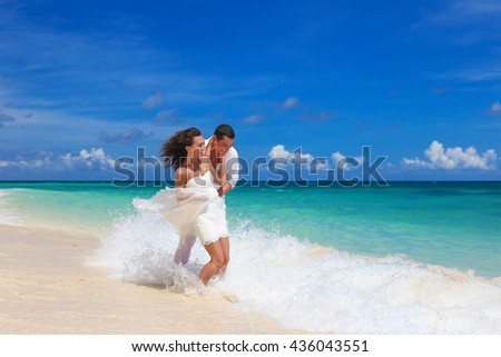 Happy beautiful bride and groom having fun and kissing at sandy tropical beach, romantic vacation. Beach wedding concept - stock photo