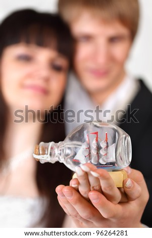 Happy beautiful bride and groom hold little vessel in bottle - stock photo
