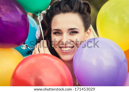 Happy beautiful bride with colorful latex balloons, outdoors. Happy young woman with big colorful latex balloons. Outdoors, lifestyle. - stock photo