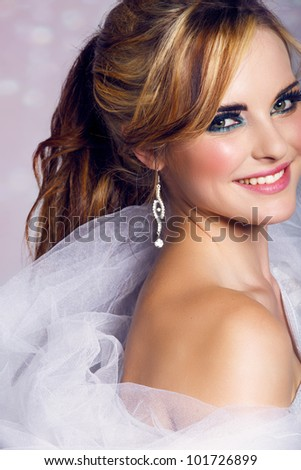 happy beautiful bride with long blond hair in ponytail waring artistic smoky eyeshadow and smiling on bokeh background. - stock photo