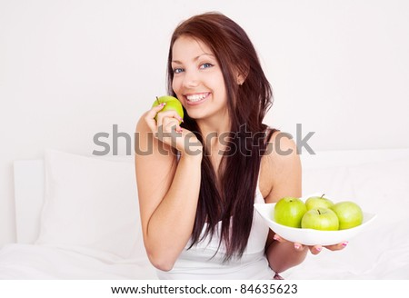 happy beautiful brunette girl  on the bed at home  eating apples