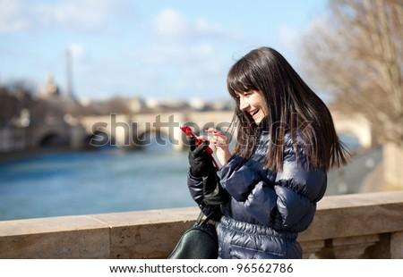 Happy beautiful brunette tourist in Paris sending an sms - stock photo