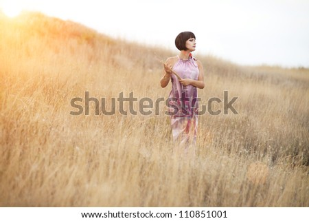 Happy beautiful brunette woman on golden wheat field in autumn nature. Alluring girl enjoying life in meadow. Romantic lady in pink dress with short hair relaxing  outdoor .Freedom concept.Countryside