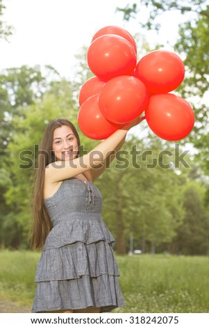 Happy, Beautiful, Carefree , Freedom Young Woman with Red  Balloons. Attractive caucasian female enjoying nature. - stock photo