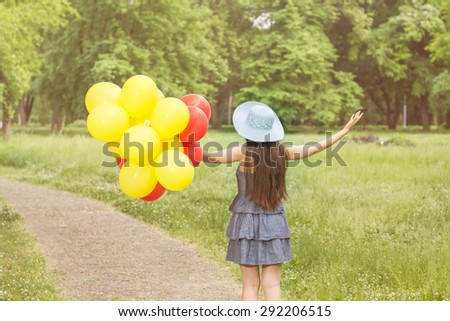 Happy Beautiful Carefree Young Woman with Red and Yellow Balloons. Attractive caucasian female enjoying nature. - stock photo