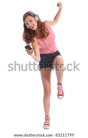 Happy beautiful caucasian teenage girl with long legs wearing denim cut off shorts, using her mobile phone listening and dancing with energy to music with silver headphones. - stock photo