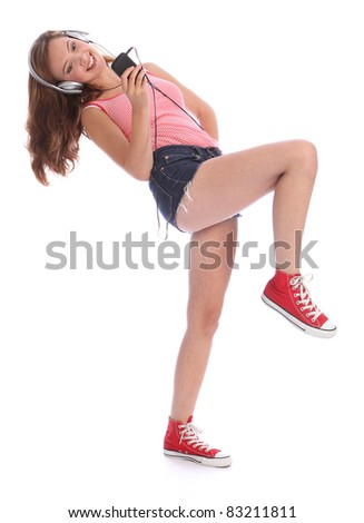 Happy beautiful caucasian teenage girl with long legs wearing denim cut off shorts, using her mobile phone listening and dancing to music with silver headphones. - stock photo