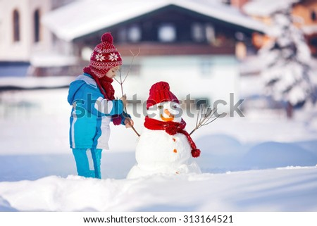 Happy beautiful child building snowman in garden, winter time - stock photo