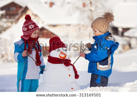 Happy beautiful children, brothers, building snowman in garden, winter time - stock photo