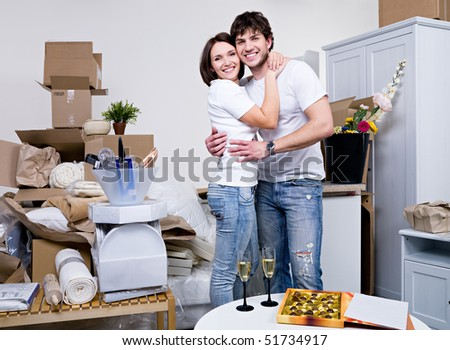 Happy beautiful couple embracing in their new flat - stock photo