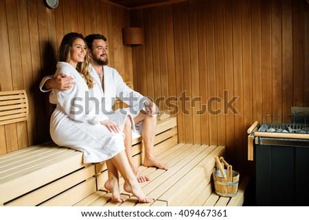 Happy  beautiful couple enjoying serene moments in sauna - stock photo