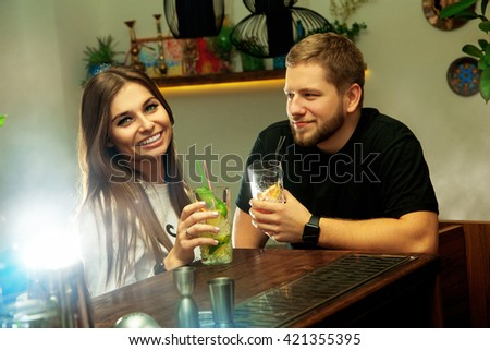 Happy beautiful couple having fun at the bar with cocktails