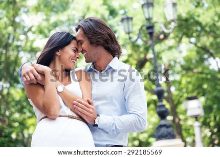 Happy beautiful couple having fun outdoors in park - stock photo