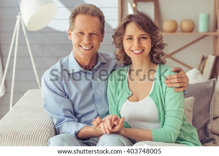 Happy beautiful couple is cuddling, looking at camera and smiling while sitting on sofa at home - stock photo