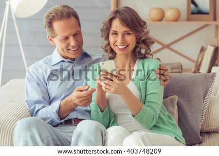 Happy beautiful couple is using a smartphone, cuddling and smiling while sitting on sofa at home - stock photo