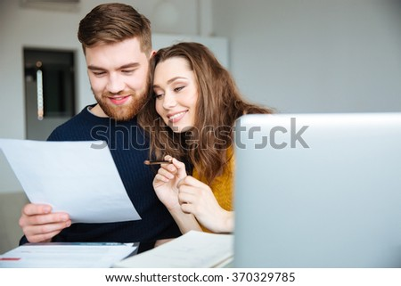 Happy beautiful couple managing their bills at home