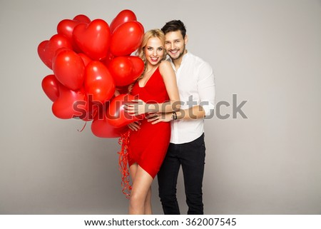 Happy beautiful couple posing on grey background and holding balloons heart. Valentine's day. - stock photo
