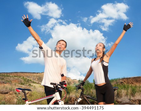 Happy beautiful couple with sporty bicycles against background of mountain landscape - stock photo
