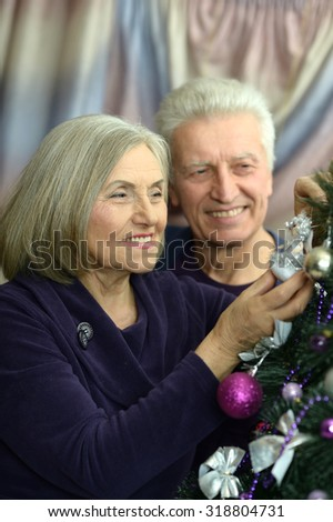 Happy beautiful elderly couple celebrating new year at home,decorated christmas tree - stock photo