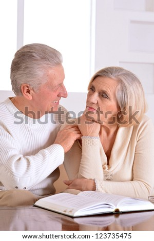 Happy beautiful elderly couple relaxing at home