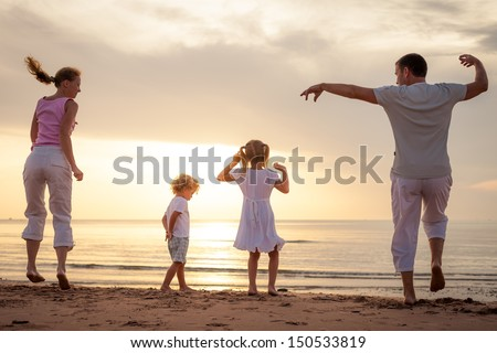 Happy beautiful family dancing at the  beach on the  dawn time. - stock photo