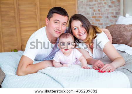 Happy beautiful family, father and mother lie on the couch with charming cute newborn baby daughter on background of cozy bedroom. Happy childhood. Background, macro, closeup - stock photo