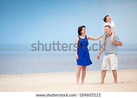 Happy beautiful family of three on tropical beach vacation - stock photo