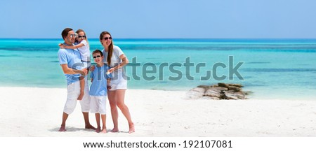 Happy beautiful family on a beach during summer vacation - stock photo