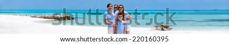 Happy beautiful family on a beach during tropical vacation, wide panorama perfect for banner - stock photo