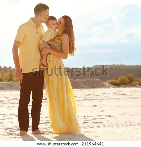 Happy beautiful family on the beach sunset  - stock photo