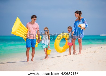 Happy beautiful family on white beach with air mattresses  - stock photo