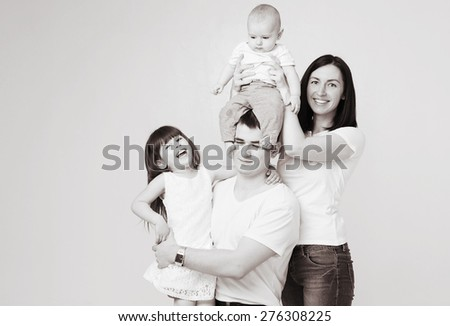 Happy beautiful family 4 people with new born baby parents sister brother portrait black and white - stock photo