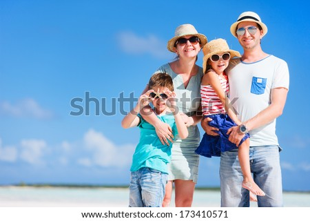 Happy beautiful family posing at beach during summer vacation - stock photo