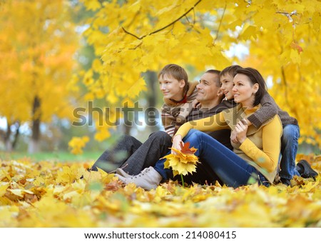 Happy beautiful family relaxing in autumn park - stock photo