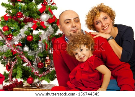 Happy beautiful family with Christmas tree sitting in embrace together - stock photo