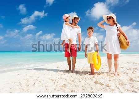 Happy beautiful family with kids walking together on tropical beach during summer vacation