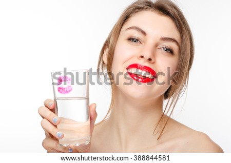 Happy beautiful female with healthy white teeth holding  the glass of  clean water with a kiss on it - stock photo