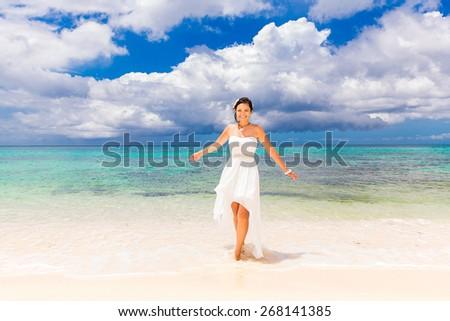 Happy beautiful fiancee in white wedding dress on shore sea. Wedding and honeymoon in the tropics. - stock photo