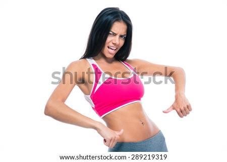 Happy beautiful fitness woman showing finger at her belly isolated on a white background - stock photo