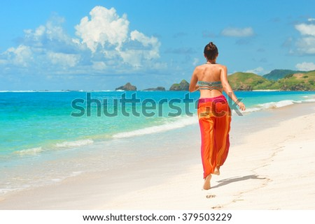 Happy beautiful free woman running on the beach, jumping playful having fun in serene picturesque near sea . 
